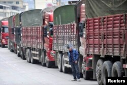 FILE - A man smokes beside trucks queuing to buy diesel at a petrol station in Luding county, Sichuan province, Oct. 23, 2011.