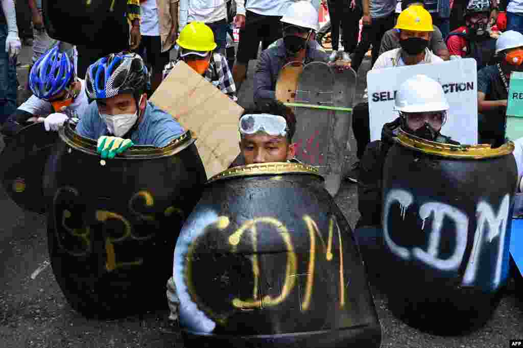 Protesters take cover behind homemade shields during a demonstration against the military coup in Yangon, Myanmar.