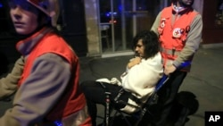 A woman being evacuated from the Bataclan theater after a shooting in Paris, Nov. 13, 2015.