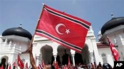 Seorang warga Aceh melambaikan bendera Bulan Sabit-Bintang dalam pawai di luar Masjid Besar Baiturrahman, Banda Aceh awal April lalu (Foto: dok). Juru bicara presiden, Julian Aldrin Pasha mengatakan Presiden SBY akan membatalkan Qanun terkait bendera dan lambang Aceh jika pemerintah setempat tidak melakukan koreksi.