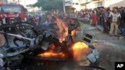 Warga Palestina di kota Gaza berkerumun di dekat mobil yang ditumpangi komandan Hamas, Ahmed al-Jaabari yang hancur akibat serangan udara Israel (14/11).