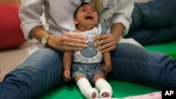 Luana Vitoria, who was born with microcephaly, cries during a physical therapy session at the Altino Ventura Foundation, a treatment center that provides free health care in Recife, Brazil, in this Feb. 4, 2016 photo. (AP Photo/Felipe Dana)
