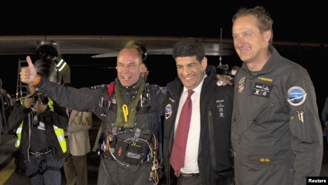 The Solar Impulse plane's project president and pilot, Bertrand Piccard (L) celebrates with co-founder and CEO Andre Borschberg (R) and Moroccan Agency for Solar Energy (MASEN) CEO Mustapha Bakkoury after the plane landed following a 19-hour flight from M
