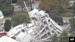 Rescue workers look for victims on the collapsed Pyne Gould Guinness building where people remain trapped after a 6.3 earthquake hit the city of Christchurch, New Zealand, February 22, 2011