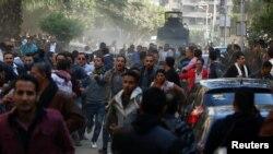 Warga Kristen Mesir bentrok dengan polisi di depan Gereja Perawan Maria dalam upacara pemakaman para korban yang tewas dalam pemboman Gereja Koptik, di Kairo (12/12). (Reuters/Amr Abdallah Dalsh)