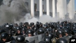 Smoke rises outside Ukraine's parliament building as riot police clash with nationalist protesters, in Kyiv, Aug. 31, 2015.