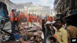 Seorang anggota Tim SAR memberikan pengumuman melalui pengeras suara di lokasi runtuhnya bangunan berlantai lima di Mumbai, India, Kamis, 31 Agustus 2017. (AP Photo/Rafiq Maqbool)