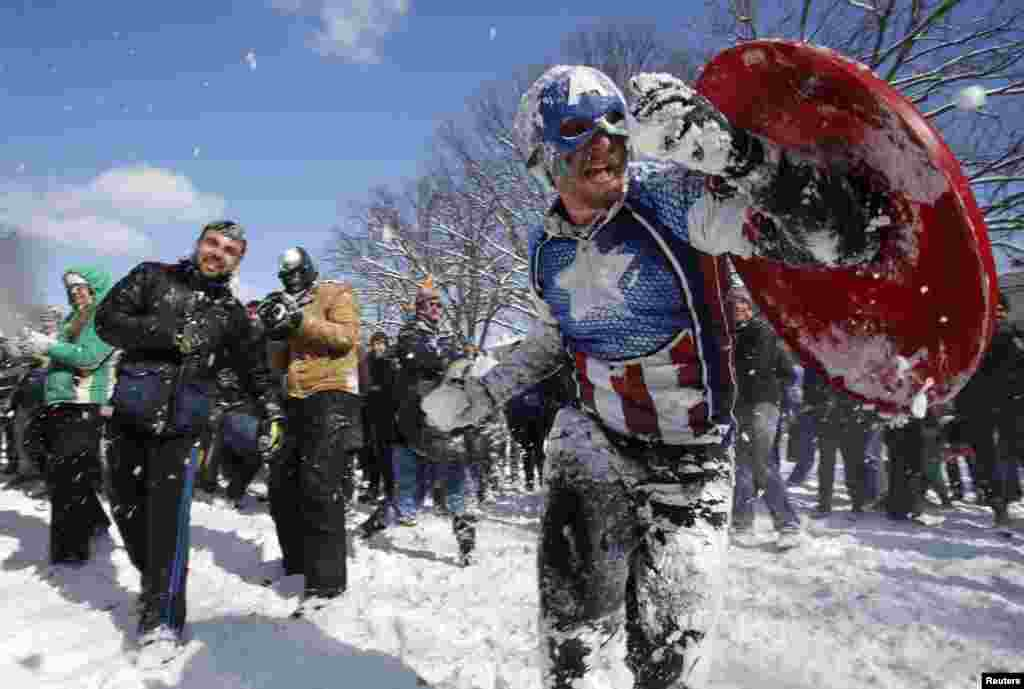 People participate in a massive snowball fight in the wake of winter storm Octavia at Meridian Park in Washington, D.C.