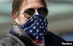 美国华盛顿一名妇女把星条旗图案的围巾当成口罩掩住口鼻。(2020年4月2日)