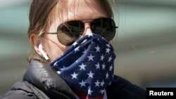 美國華盛頓一名婦女把星條旗圖案的圍巾當成口罩掩住口鼻。(2020年4月2日)