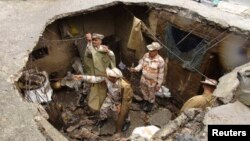 Indo-Tibetan Border Police personnel search for flood victims in a damaged house in Uttarkashi in the Himalayan state of Uttarakhand, June 26, 2013.