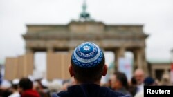 FILE - A man wearing a Jewish scullcap waits for the start of an anti-Semitism rally at Berlin's Brandenburg Gate, in Berlin, Germany Sept. 14, 2014.