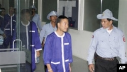 Panich Vikitsreth, center, a member of Thailand's Parliament , is escorted by Cambodian court security personnel upon his workout at Phnom Penh Municipal Court on Thursday.