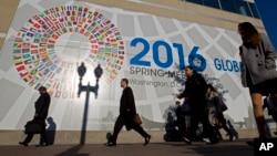 有人在国际货币基金组织总部外面走过(2016年4月14日)。墙上有各国国旗图案。