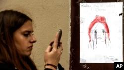 A woman checks her smartphone by a poster showing a weeping image of Marianne, symbol of the French Republic, near Le Carillon restaurant, a site of terrorist attacks, in Paris, Nov. 17, 2015. The attacks have triggered waves of social media communication