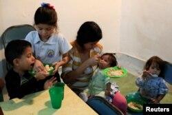 The children of Viviana Colmenares (C) have lunch in a community diner at the slum of Petare in Caracas, Feb. 22, 2018.