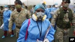 Agents de santé escortés par des soldats lors d'une campagne de dépistage de la COVID-19 dans le bidonville Villa Maria del Triunfo, Lima, Pérou, 12 janvier 2021. (Photo AP/Martin Mejia)
