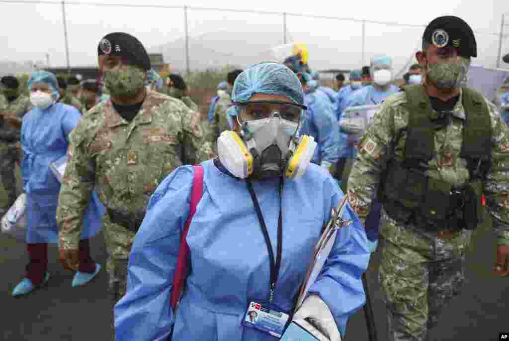 Health workers are escorted by soldiers during a house-to-house COVID-19 testing campaign in the Villa Maria del Triunfo shantytown of Lima, Peru.