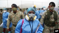 Les agents de santé sont escortés par des soldats lors d'une campagne de dépistage du COVID-19 porte-à-porte dans le bidonville Villa Maria del Triunfo de Lima, au Pérou, le mardi 12 janvier 2021. (Photo AP / Martin Mejia)
