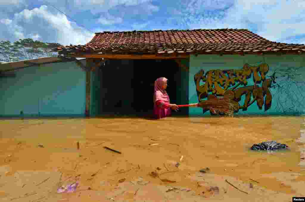 A woman villager cleans garbage in front of her house as flood hits Tanjungsari village in Tasikmalaya, Indonesia.