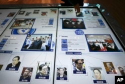 FILE - A visitor, top, looks at an electronic screen showing images and convicted corruption charges of China's fallen politicians, Bo Xilai, bottom second right, Zhou Yongkang, bottom left, and other senior officials, at the China Court Museum in Beijing.