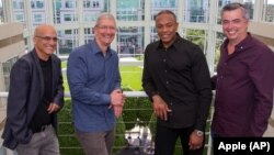 From left, music entrepreneur and Beats co-founder Jimmy Iovine, Apple CEO Tim Cook, Beats co-founder Dr. Dre, and Apple senior vice president Eddy Cue pose together at Apple headquarters in Cupertino, Calif., May 28, 2014.