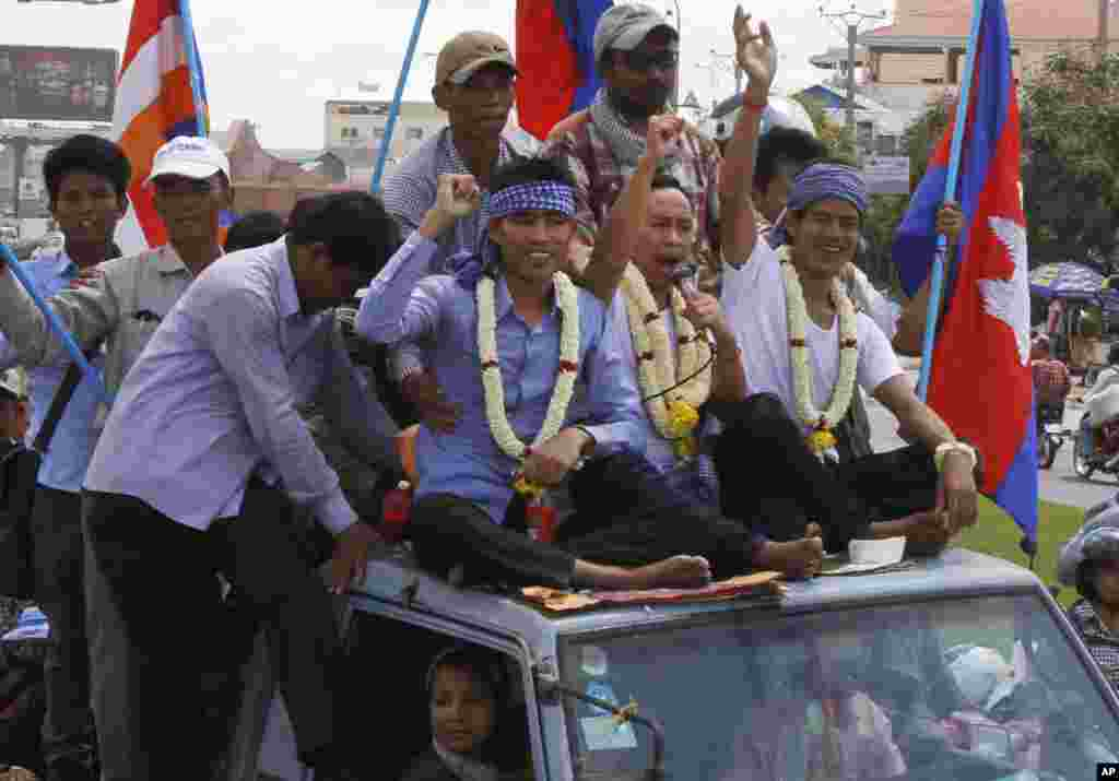 Anti-government protesters who had been in prison since their arrest in January wave from atop a truck during a rally in Phnom Penh, Cambodia, May 30, 2014.