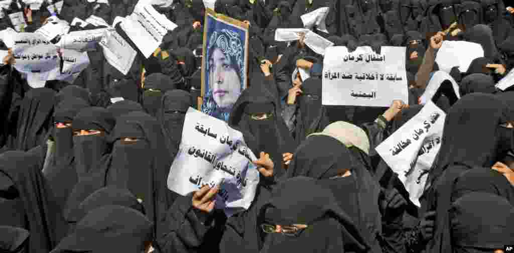 "January 2011: Yemeni women hold placards and a photograph of activist Tawakkul Karman during an anti-government rally in Sanaa. Placards read in Arabic, ""Arresting Karman is an unethical incident against Yemeni Women."""