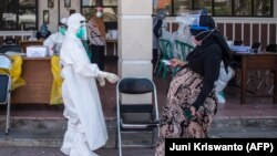 Seorang ibu hamil datang untuk tes swab virus corona COVID-19 di Surabaya pada 21 Juli 2020. (Foto: AFP/Juni Kriswanto)