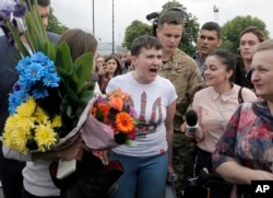 FILE - Ukrainian pilot Nadiya Savchenko, center, speaks to the media upon her arrival at Boryspil airport outside Kyiv, Ukraine, following her arrival from Russia in a prisoner swap, May 25, 2016.