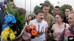 Ukrainian pilot Nadezhda Savchenko, center, speaks to the media upon her arrival at Boryspil airport outside Kiev, Ukraine, May 25, 2016.