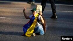 Una joven opositora se sienta para bloquear una calle en Caracas durante las protestas antigubernamentales.