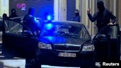 Policías belgas se organizan para realizar un allanamiento en un suburbio de Molenbeek, Bruselas, relacionado con los atentados de París.