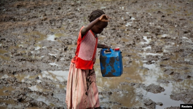 A girl walks through mud to get water at the Yusuf Batil refugee camp in Upper Nile, South Sudan, July 4, 2012.