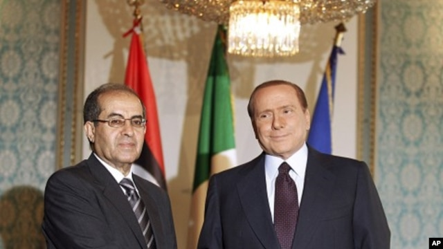 Italian premier Silvio Berlusconi, right, shakes hand with Mahmoud Jibril, deputy chairman of the Libyan National Transitional Council, at the prefecture building in Milan, Italy, August 25, 2011