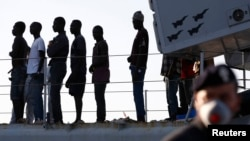 FILE - Migrants disembark from a navy ship in the Sicilian harbour of Pozzallo June 30, 2014.