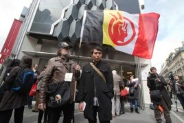 A French supporter of the Indian cause, left, holds a flag of the American Indian Movement and an American exchange student, member of Arizona's Hopi tribe, Bo Lomahquahu, right, stand outside of the Druout's auction house in Paris, April 12, 2013.
