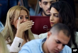 Marwa Fahmy, wife of Canadian Al-Jazeera English journalist Mohammed Fahmy, left, sitting with human rights lawyer Amal Clooney, bursts into tears as the verdict is read in a courtroom in Tora prison in Cairo, Egypt, Aug. 29, 2015.