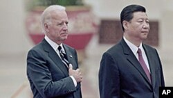 Chinese Vice President Xi Jinping, right, and his U.S. counterpart Joseph Biden listen to national anthems during a welcoming ceremony inside the Great Hall of the People in Beijing, August 18, 2011