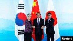左起:韩国外长康京和、中国外长王毅和日本外相河野太郎在北京举行的中日韩三国外长会议上握手。(2019年8月21日))