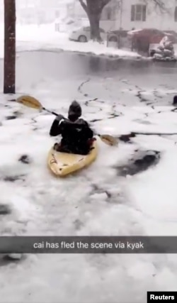 A person kayaks along a flooded street in Winthrop, Massachusetts, in this image taken from a Jan. 4, 2018, social media video. @odriscoll99/via Reuters
