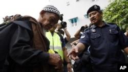 Cảnh sát Malaysia kiểm tra danh tính của một người đàn ông ở Kuala Lumpur.