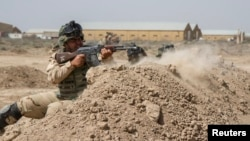FILE - Iraqi soldiers train with members of the U.S. Army 3rd Brigade Combat Team, 82nd Airborne Division, at Camp Taji, Iraq, in this U.S. Army photo released June 2, 2015.