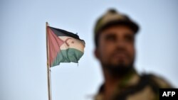 Uniformed soldier of the pro-independence Polisario Front stands before a Sahrawi flag flying at the Boujdour refugee camp near the town of Tindouf in Western Algeria on Oct.17, 2017.