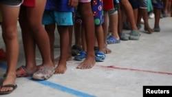 Niños migrantes venezolanos hacen fila dentro de un coliseo donde se instaló un campamento temporal en Arauquita, Colombia, el 26 de marzo de 2021.