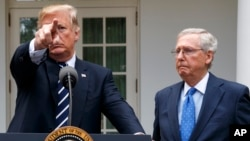 President Donald Trump calls on a reporter as Senate Majority Leader Mitch McConnell, R-Ky., watches in the Rose Garden of the White House, Oct. 16, 2017
