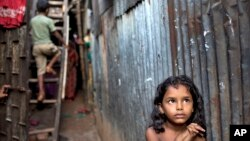 A Bangladeshi child stands in an alley as a boy climbs a ladder outside their home at a slum in Dhaka, Bangladesh, Oct. 17, 2014.