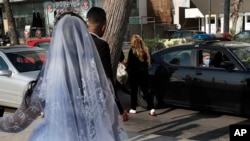 FILE - In this April 18, 2020 file photo, a policeman asks a bride and groom to leave the waterfront promenade where they had decided to take some pictures, in Beirut, Lebanon.