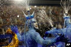 FILE - Performers from the Portela samba school sport waterspouts on their heads during Carnival celebrations at the Sambadrome in Rio de Janeiro, Brazil, Feb. 9, 2016.