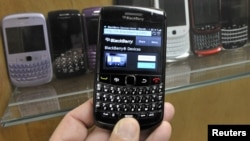 A BlackBerry device is shown in front of products displayed in a glass cabinet at the Research in Motion offices in Waterloo November 14, 2012.